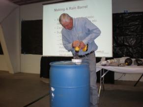 Billy Kniffen drills a barrel for rain.